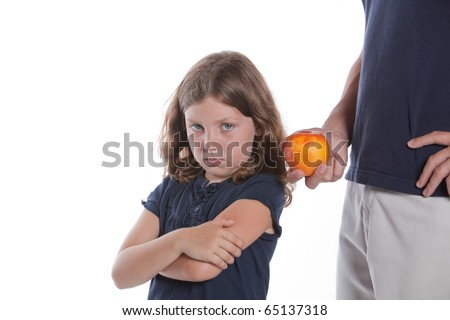 A cute little girl turns away as her father offers her a healthy snack apple