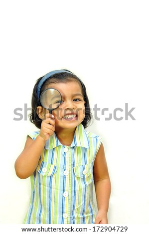 A cute little girl using a magnifying glass - stock photo