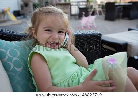 A cute little girl wearing a green dress using a cellular phone. - stock photo