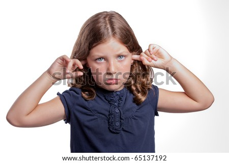 a cute little girl with big blue eyes covers her ears while making a sad face - stock photo