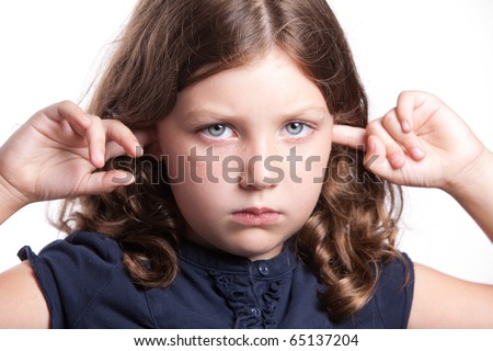 a cute little girl with big blue eyes covers her ears while making a sad face