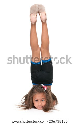 A cute little gymnast does exercises on the white background - stock photo