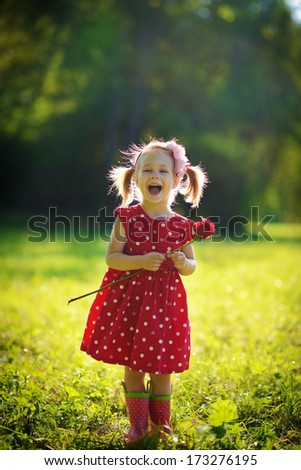 A cute little happy girl holding a red rose in the green meadow on a sunny summer day - stock photo