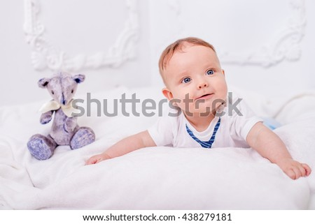 A cute little naked baby is looking into the camera on the white wall with teddy - stock photo