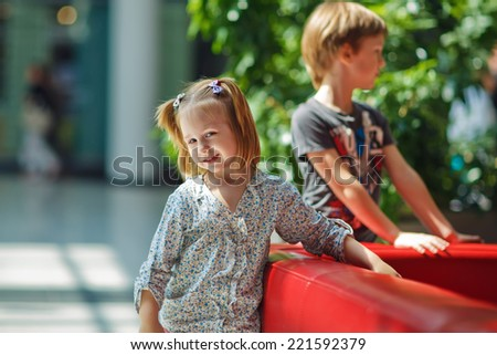 A cute little smiling girl reclining on a red couch in a huge mall  - stock photo