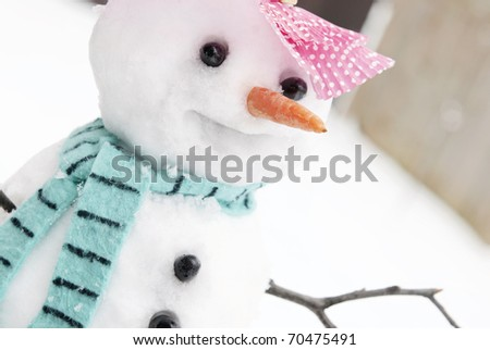 A cute little snowman with a happy face,  closeup horizontal with shallow depth of field - stock photo