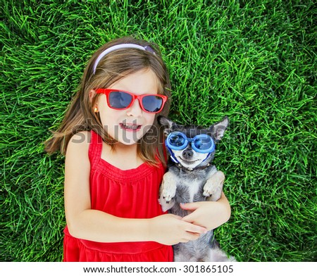 a cute little toddler girl with red sunglasses on holding a tiny chihuahua with blue goggles on laying in the grass in a park or backyard with a nice green lawn  - stock photo