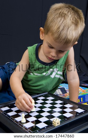 A cute little 3 year old boy playing on a black background. - stock photo