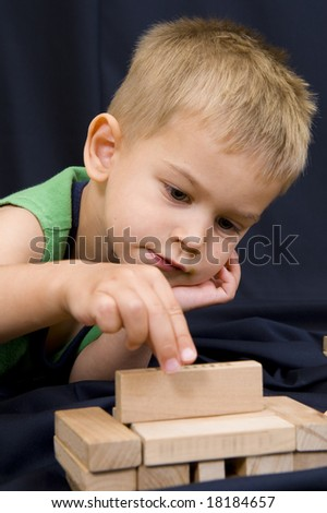 A cute little 3 year old boy playing on a black background with some wooden blocks. - stock photo