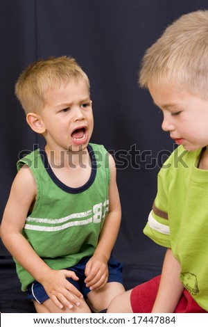 A cute little 3 year old boy shouting angrily at his 5 year old brother. - stock photo