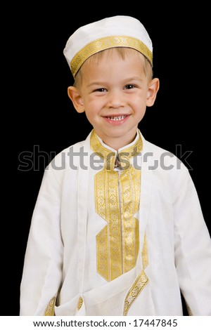A cute little 3yr old boy wearing a traditional Arabian thobe or dishdasha for the purpose of asking for Ramadan treats. Isolated on Black. - stock photo