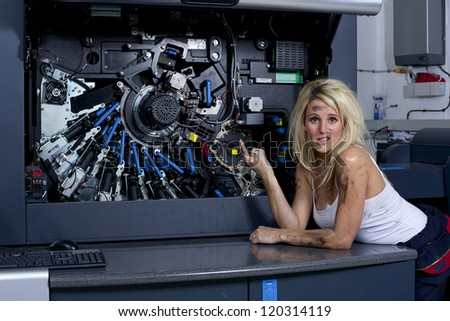 A cute looking blonde woman servicing a digital printing press, gets covered in grease and ink. - stock photo