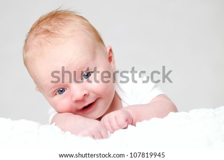 A cute newborn / 4 weeks old baby on a white carpet. Looking up with a very happy face laughing - stock photo