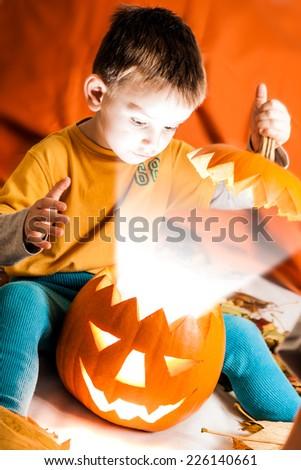 A cute photograph of a boy and her lighting Halloween pumpkin - stock photo