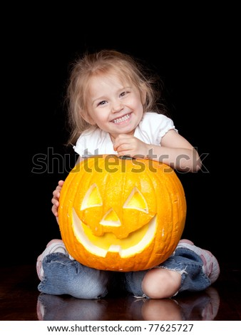 A cute photograph of a girl and her pumpkin.