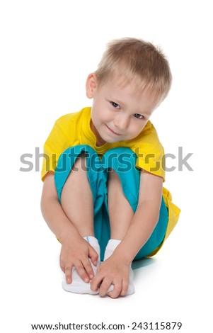 A cute preschool boy sits on the white background - stock photo