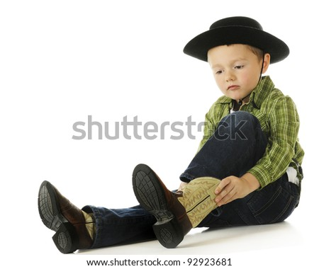 A cute preschool cowboy putting on his boots.  On a white background. - stock photo