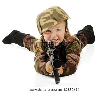A cute preschool girl in army camouflage laying on the floor aiming her machine gun.  Isolated on white. - stock photo