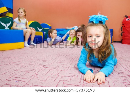 A cute preschool girl lying, her friends in the background