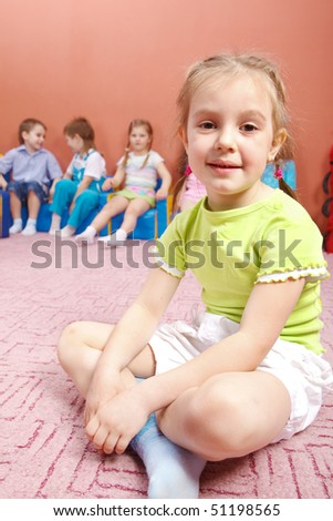 A cute preschool girl sitting, her friends in the background