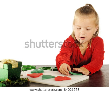 A cute preschooler happily cutting out red and green children's dough cookies for Christmas.  Image has plenty of white space for your test. - stock photo
