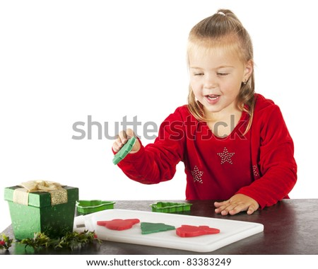 """A cute preschooler happily making Christmas """"cookies"""" from colorful kiddie dough. - stock photo"""