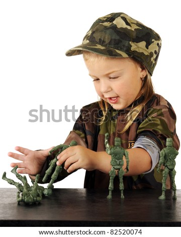 A cute preschooler in army garb playing with toy soldiers on a counter top. - stock photo