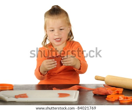 A cute preschooler making Halloween cutouts using modeling clay, a rolling pin and cookie cutters. - stock photo