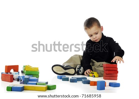A cute preschooler playing with blocks and small wooden vehicles.  Isolated on white.