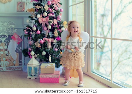 A cute red-haired little girl with angelic wings and pretty skirt standing near the magnificent Christmas tree and presents under it in the large light room with a fireplace and a large window - stock photo
