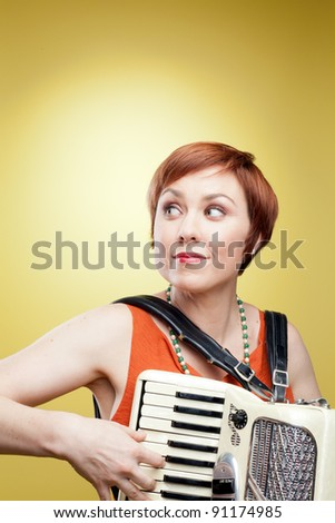 A cute redheaded woman playing an accordion. Photographed with studio light in front of a yellow backdrop. - stock photo