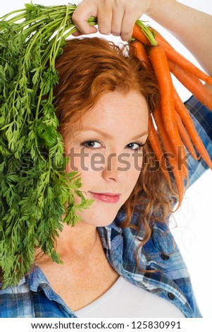 A cute redheaded woman with freckles holding fresh carrots - stock photo