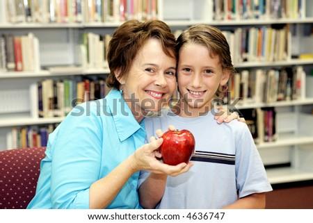 A cute school boy giving his teacher an apple. - stock photo