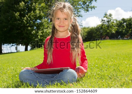 A cute schoolgirl sitting on a green lawn in summer park, holding  tablet computer - stock photo