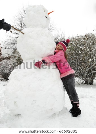 A cute small happy  girl posing with her big snowman. - stock photo