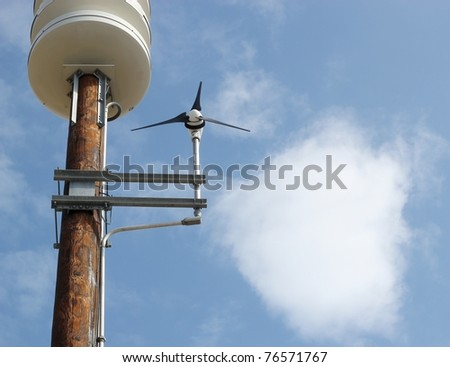 A cute small wind power generator against a bright blue sky with a round cloud