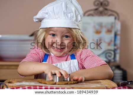 A cute smiling boy is baking and cutting out gingerbread shapes - stock photo
