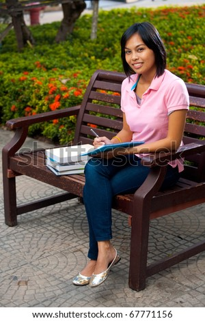 A cute smiling college student on a university campus bench writes into her notepad - highish angle.  20s female Asian Thai model of Chinese descent. - stock photo