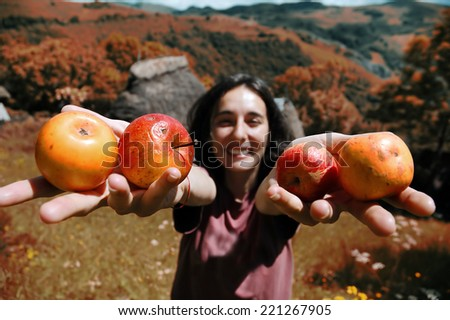 A cute, smiling girl holding apples in her hand - stock photo
