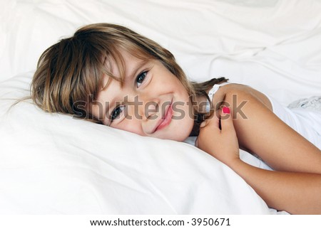 A cute smiling girl relaxing in a bed - stock photo