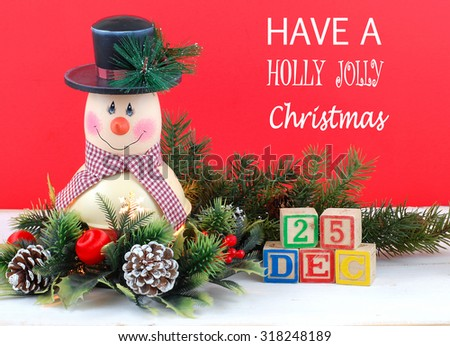 A cute snowman decoration with lamp inside is surrounded by holly, pine, pine cones and Christmas decorations. Bright red background. Have a Holly Jolly Christmas message with Dec. 25 in letter blocks - stock photo
