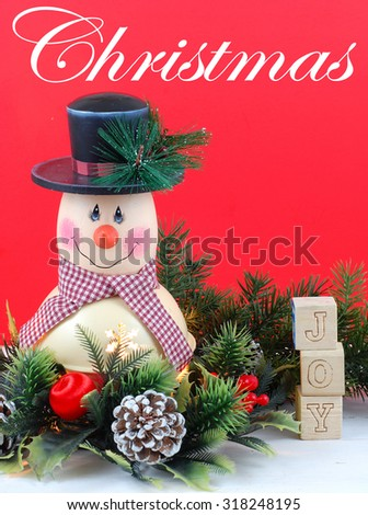 A cute snowman decoration with lamp inside is surrounded by holly, pine, pine cones and Christmas decorations. Bright red background. Christmas text and letter blocks spelling joy