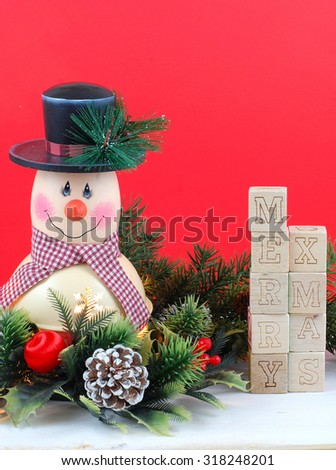 A cute snowman decoration with lamp inside is surrounded by holly, pine, pine cones and Christmas decorations. Bright red background. Merry Xmas message with letter block. Copy space upper right - stock photo