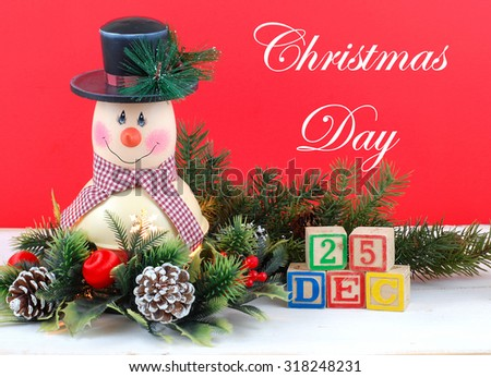 A cute snowman decoration with lamp inside is surrounded by holly, pine, pine cones and Christmas decorations. Bright red background. Christmas Day Dec 25 using text and letter blocks - stock photo
