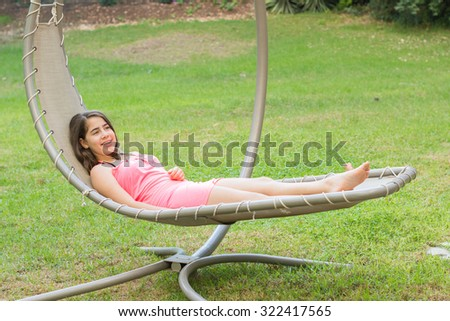 A cute teenage girl, young woman, with braces on her teeth, enjoying the fresh mountain air on a modern outdoor hammock swing in the Galilee in the north of Israel