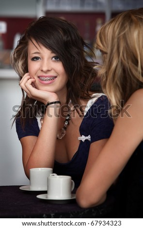 A cute teenaged girl with braces sitting at a table with a friend. - stock photo