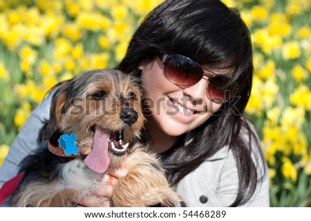 A cute terrier mix breed pup in the arms of a beautiful pet owner. Shallow depth of field with sharp focus on the dog's nose. - stock photo
