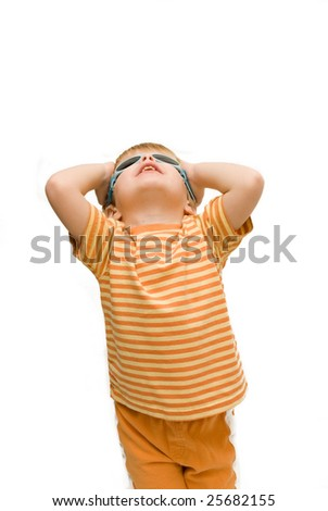 A cute three year old boy wearing summery clothes and sunglasses looking upwards. - stock photo