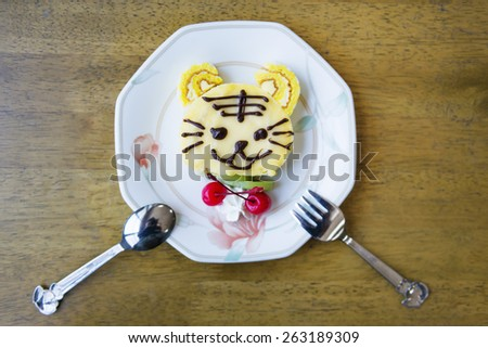 A cute tiger cartoon decorated cake.  - stock photo
