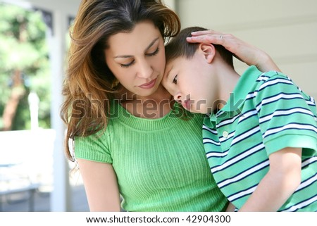 A cute tired boy and his mother on the porch at home showing love - stock photo